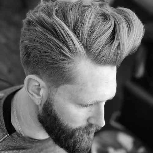 copete largo en forma hacia arriba con low fade y barba llena